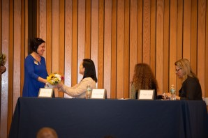 Housing Families Director of Community Engagement Patty Kelly presents thank you bouquets to the panelists at this week's Breaking Barriers Breakfast.