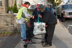 Carl Durham assisted Jose Medina with his cart outside the Grace Food Pantry on Sunday morning
