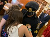 His daughters, Jacinda, 6, and Delaney, 9, close the clasp of his pin, which is for sergeants.