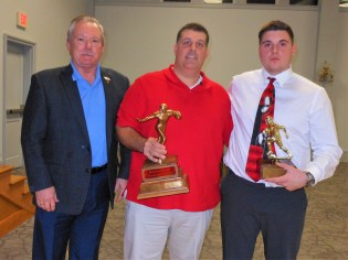 """PRESENTING THE PRIZES: Left to right, John Smolinsky of the Saugus Lions Club, Saugus High School Coach Mike Mabee and Co-Captain Jake Morgante – this year's recipient of the Saugus Lions Club """"Heisman Award"""" – pause after the presentation of the trophy at the club's 46th Annual Football Meeting and Dinner, which was hosted on Wednesday night (Nov. 14) by the Peabody Lions Club at the Holy Ghost Society Hall in Peabody. Mabee holds the giant """"Heisman Trophy,"""" which lists all past winners from Saugus High. The dinner, which bonds senior football players from Saugus and Peabody, is considered a friendly gathering of the two schools before their rivalry showdown on Thanksgiving Day. This year's game will be played next Thursday (Nov. 22) at 10 a.m. at Peabody Veterans Memorial High School. (Saugus Advocate Photos by Mark E. Vogler)"""