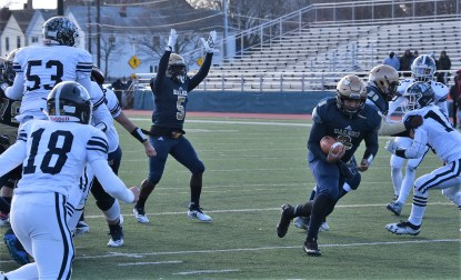 UPSET VICTORS: Sophomore wide receiver Justin Nortelus (#9) burst through the Medford defensive line while junior receiver Jerry Mervil cheers him on during the Golden Tornadoes' Thanksgiving Day 28-24 upset win over Medford. (Advocate photo by Ross Scabin)