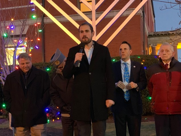 During Tuesday's Menorah Lighting Ceremony, Jewish Orthodox Rabbi Sruli Baron of Congregation Tifereth Israel (center), explained how Chanukah originated. (Advocate photos by Tara Vocino)