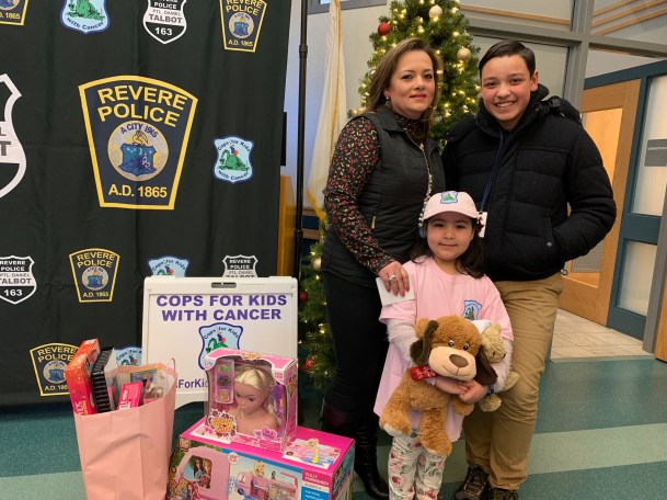 Recently, Cops for Kids with Cancer gave Christmas gifts, including Barbies, stuffed animals and board games, for cancer survivor Emilia Alvarez, 6, to unwrap at the police station. At left are Emilia's mother, Claudia Cardona; Emilia, in center; and her brother, Lukas Diaz, 13.