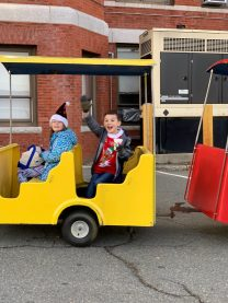 James Keenan, 10, waves as he rides the train during Saturday's Santa Walk event. At right is Anna Doucette, 9.