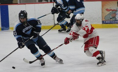 Saugus's Dante McGrane reaches over in an attempt to steal the puck from a Medford forward. (Advocate photos by Greg Phipps)