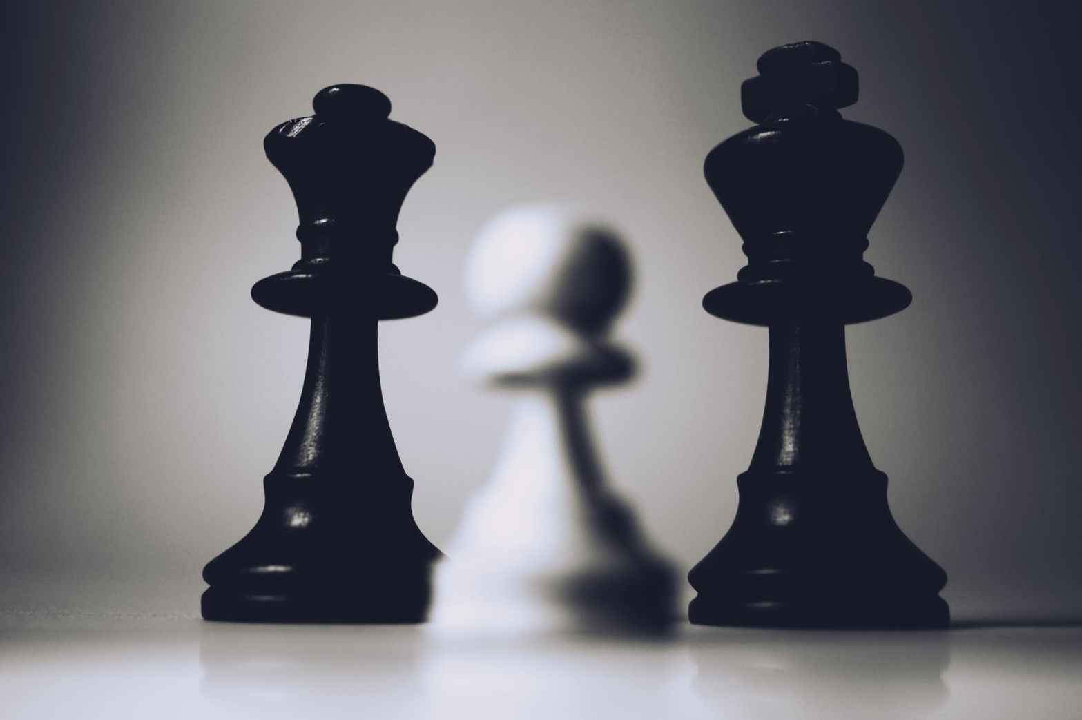 selective focus photo of two black chess pieces
