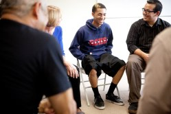 Smiling young man surrounded by adults sitting in chairs giving encouraging smiles.