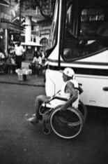Homem idoso de cadeiras de rodas, usa bone, regata e bermuda anda no meio da rua andando junto com os ônibus