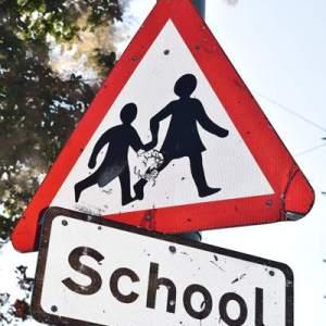 Panneau de sécurité routière : attention école. Un adulte tient la main à un enfant. Il veille sur lui à l'image de l'AEEM Pau Béarn.
