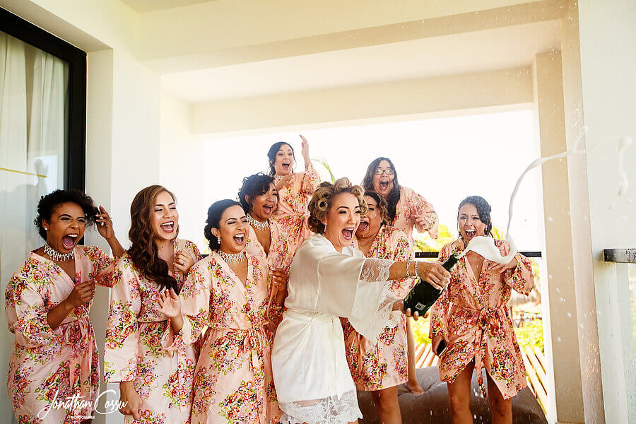 Bride to be pops the bubbly. Finest Playa Mujeres Wedding by Jonathan Cossu Photographer