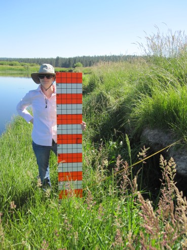 Jenn poses for the camera with the coverboard to document frontal vegetation cover.