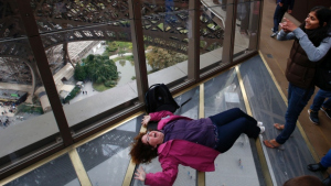 Woman photographing friend who is lying on Eiffel Tower's new glass floor.