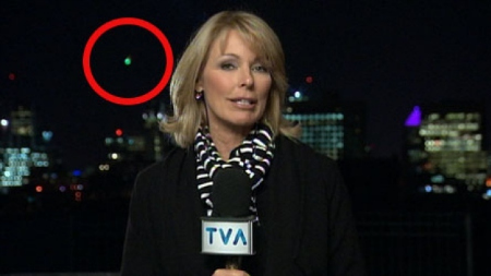 Green light inside red circle near reporter's head.