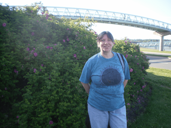 Cathi with flowers and a bridge.