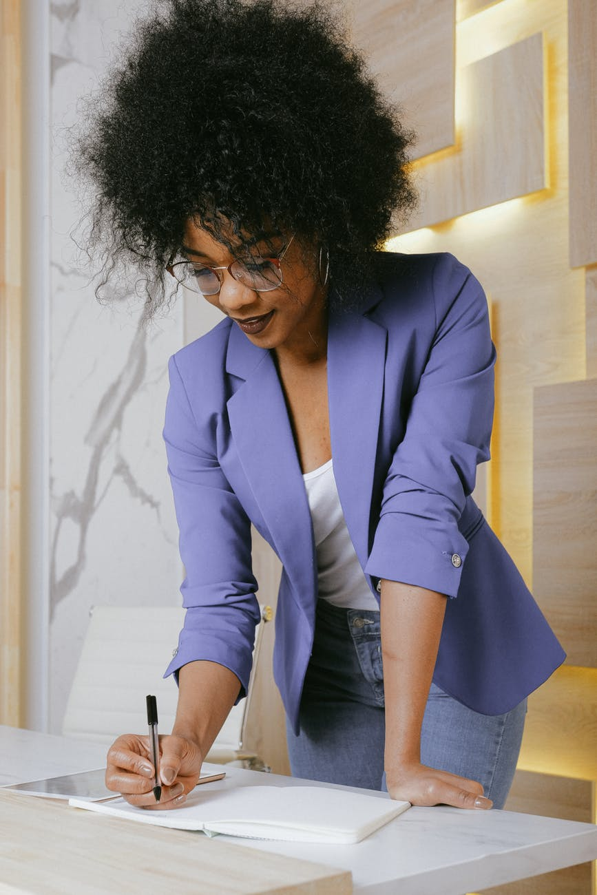 Image of Black woman writing, image in use for article Sequel Writing for Beginners.