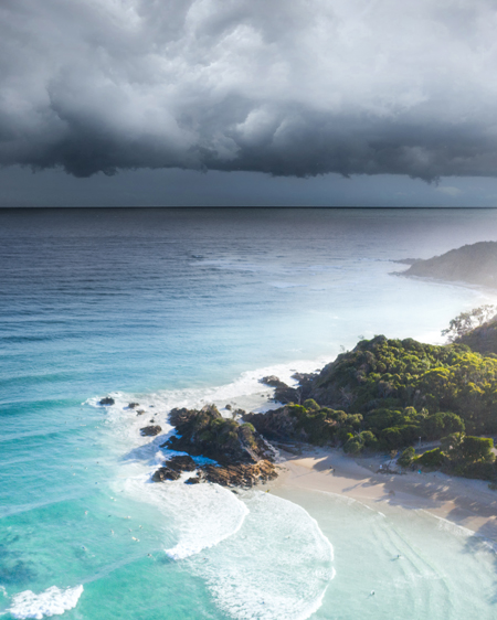 Dark Clouds Over Lush Green Hills And Bright Blue Waters