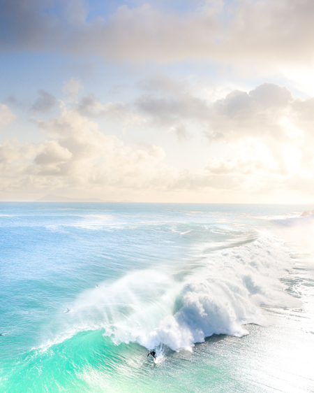 Aerial Of A Surfer On A Bright Blue Wave At Sunrise