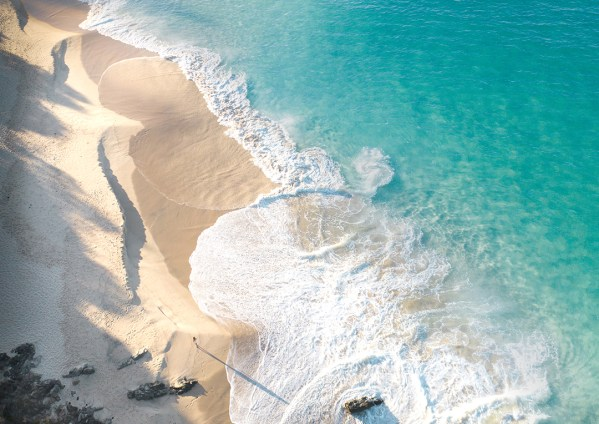 Aerial of Turquoise Wave Rolling Onto Shore