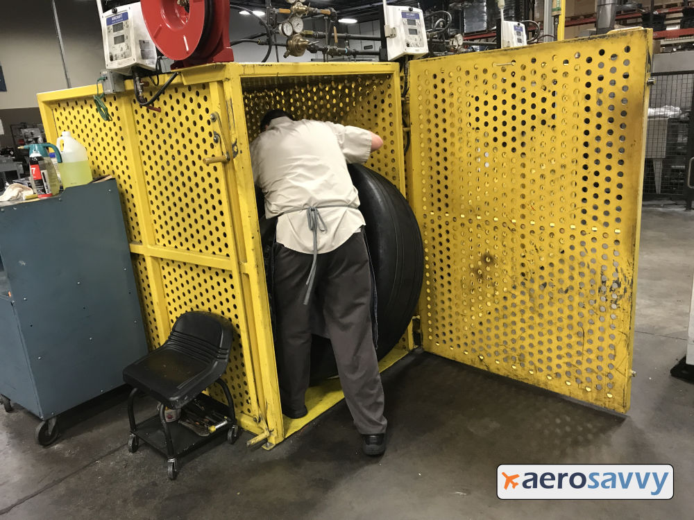 Technician rolls a tire into the open cage. Door swings open and closed