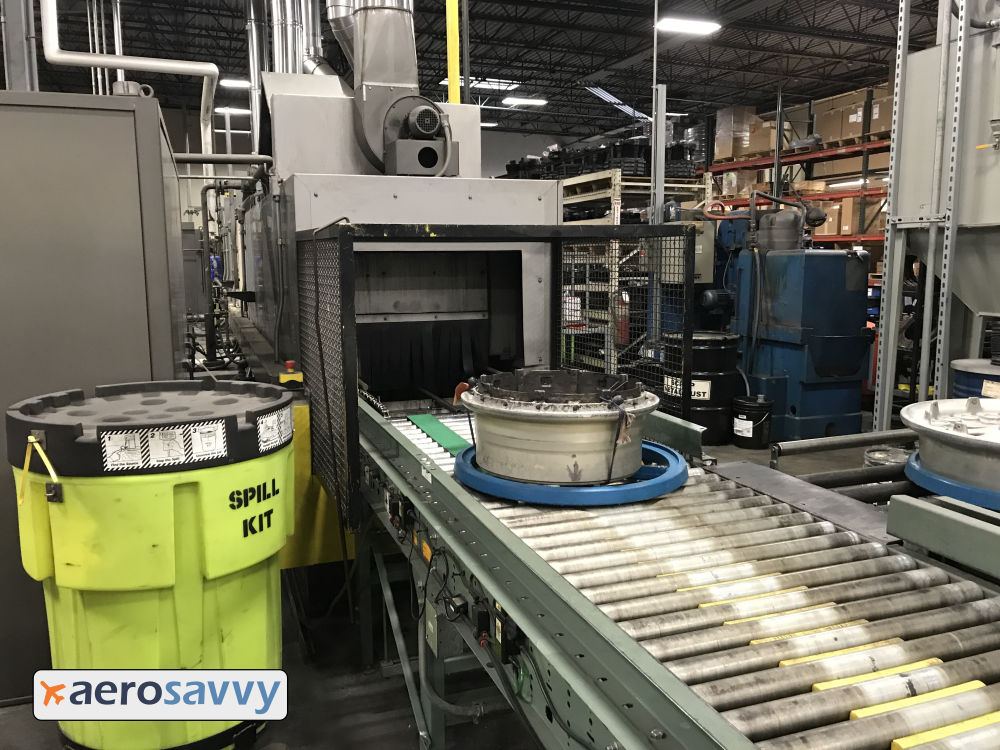 conveyor belt made with metal rollers directs a tray of wheel parts into an industrial washer.