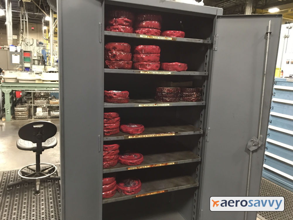 Open metal cabinet with 20 or 30 sets of wheel bearings, each wrapped in red plastic.