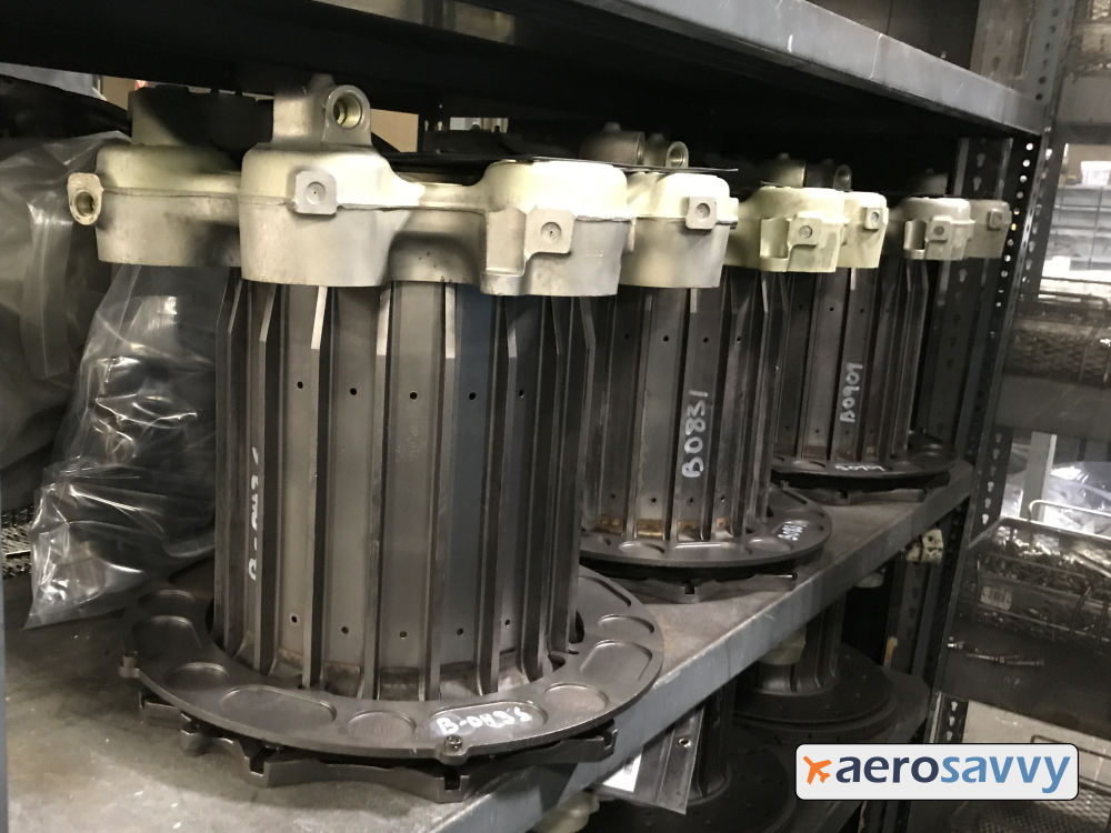 shelf with several brake cores. Cores are clean metal with white hydraulic actuators mounted on top