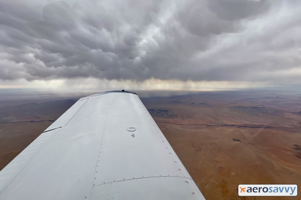 view over left wing. Dark clouds with rain falling, but most evaporation before hitting ground