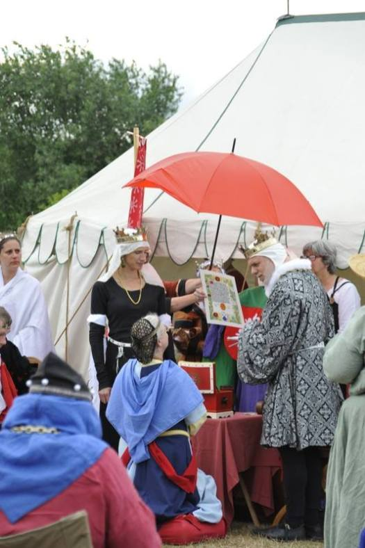 THL Mairghead receives her Fleur scroll and a Millrind. Photo by Baron Steffan.