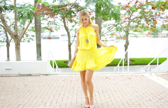 Miami Fashion blogger, Amanda Tur from A Fancy Affair is wearing a shop Alexis Monic yellow dress paired with a blue Bourbon & Boweties with tassel necklace and gucci soho nude patent clutch and Banana Republic gold Rakel wedges and Michele Deco 20mm watch with the nude band