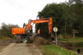 Een waterafvoerbuis naast de weg wordt uitgegraven