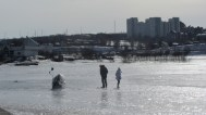 Man and daughter play on the frozen river.. What's that plastic bag next to them?...