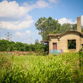 Abandoned Gary depot with graffiti along train tracks during the summer