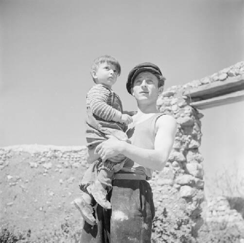 Vader met kind op de arm  op de plek waar het gezin hun huis zal gaan bouwen. De…