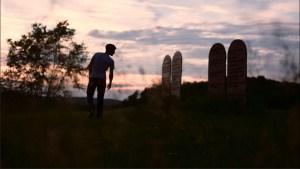 Young man looking at epitaphs at sunset