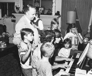 Jerry Coniker and his young children gathered around the piano; the lived Coniker family's Catholic faith is an example for us all.