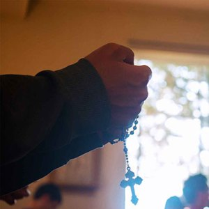 Youth Retreat praying hands with rosary