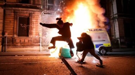 a skateboarder does a trick in front of a burning police van in Bristol