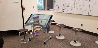 whiteboards on the wall with stools, desks and magnets