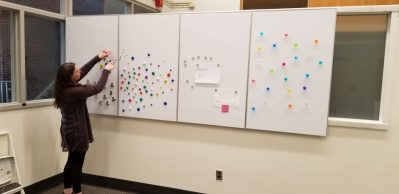woman using whiteboards on the wall with magnets