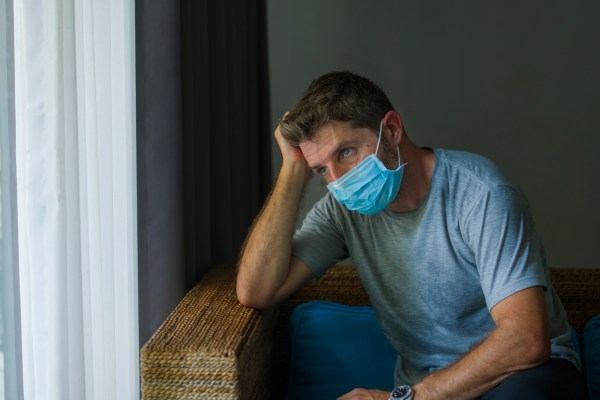 covid-19 virus lockdown - sad and worried man in medical mask thinking and feeling scared in quarantine following stay at home instructions to contain virus pandemic