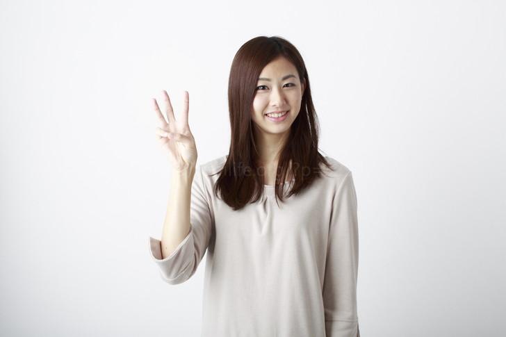 3本指を立てる女性