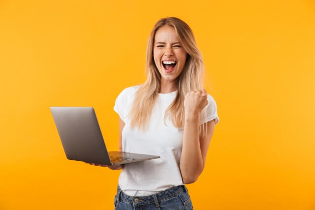 パソコンを持ってガッツポーズの女性 (1)