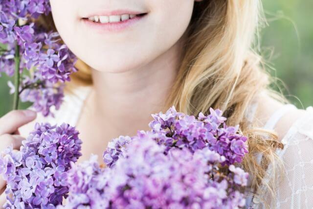 女性の口元と花
