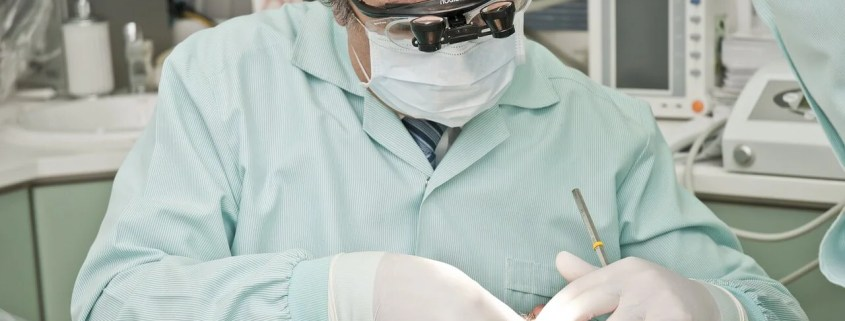 Dentist performs an emergency dental extraction on a sedated patient