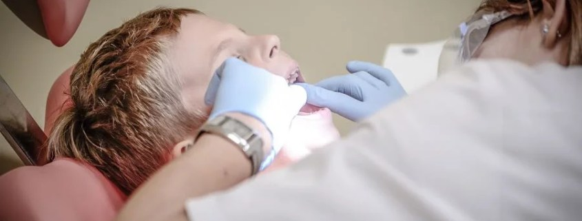 boy sits in dentists chair while the dentist examines his teeth
