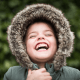 Young boy wearing a green parka and laughing