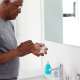older black man stands in his bathroom about to floss his teeth