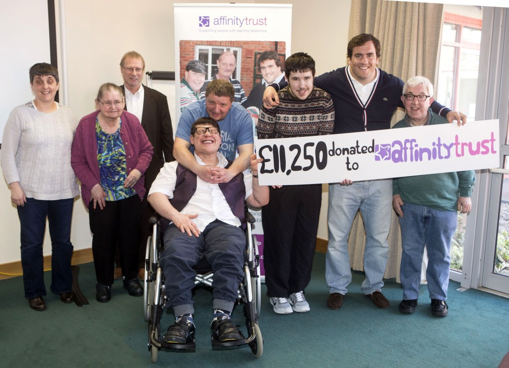 "Marcos and several people we support holding a banner that reads ""£11,250 donated to Affinity Trust"""