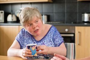 Woman with learning disabilities sitting in a kitchen, holding a mug