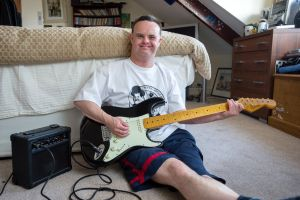 Man playing an electric guitar in his bedroom